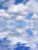 Abstract of a blue sky with alto cumulus clouds reflected over water. poster