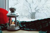 Winter background-lantern with candle and plaid with pillow on windowsill and winter scene outdoors. Still life with winter concept Winter evening with cold winter weather outdoors. Winter composition poster