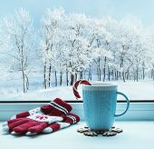 Winter Christmas background. Christmas still life. Cup with Christmas candy cane on windowsill and winter trees outdoors. Winter festive composition with Christmas mood, winter Christmas still life poster