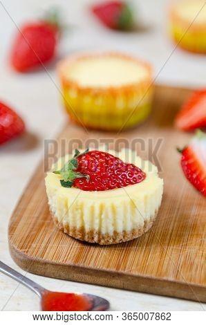 Mini Strawberry Cheesecake On A Bamboo Cutting Board.