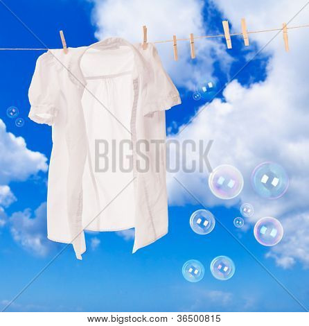 White shirt hanging on washing line with soap bubbles against a blue sky