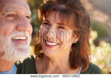 Loving Senior Hispanic Couple Hiking Along Trail In Countryside Together