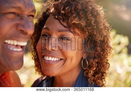 Loving Senior African American Couple Hiking Along Trail In Countryside Together