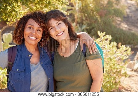 Portrait Of Two Senior Female Friends Hiking Along Trail In Countryside Together