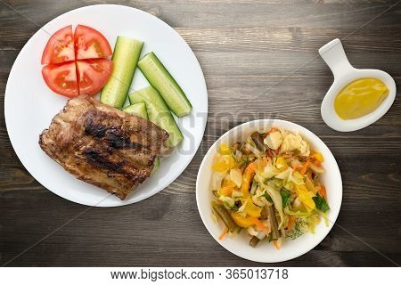 Grilled Pork Ribs With Sliced Cucumbers And Tomatoes On A White Plate. Pork Ribs On Black Wooden Bac