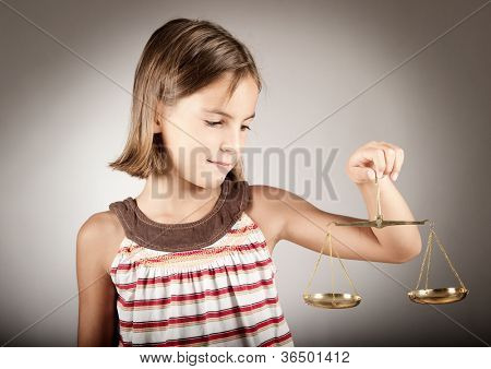 little girl holding justice scale