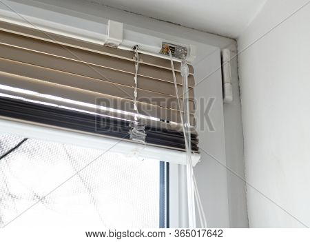 Stuck Blinds.adjusting The White Blinds In Height Use A Cord.half-open Metal Blinds Mounted On A Pla