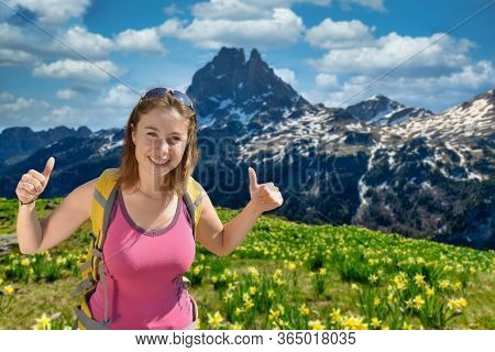 Pretty Hiker Woman With Pic Du Midi Ossau And Daffodils In Springtime, French Pyrenees