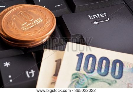 Japanese Money Is On The Black Keyboard Of A Computer Or Laptop Near The Enter Button. 100 Yen Coin