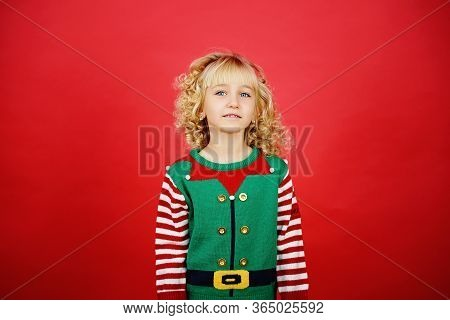 Merry Christmas Little Girl In Santa Elf Helper Costume On Bright Red Vivid Color Background. Red An
