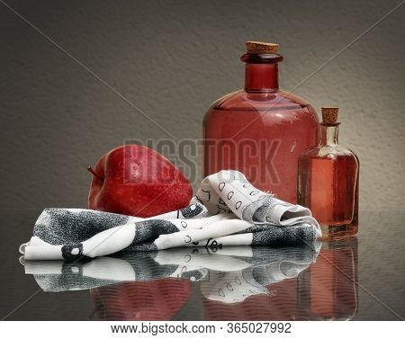 Still Life With Ripe Red Apple, Black And White Napkin And Two Vintage Glass Bottles With Homemade A