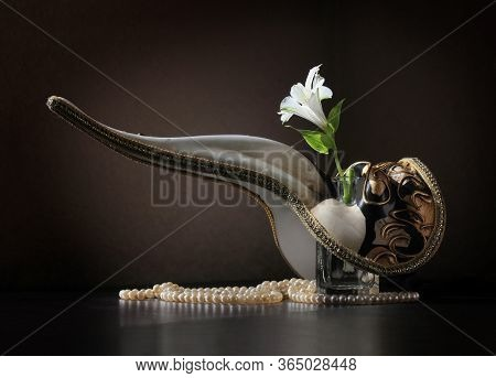 Retro Style Still Life With Beaked Venetian Carnival Plague Doctor Mask, Alstroemeria Flower In The
