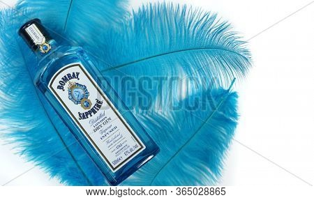 Prague, Czech Republic- February 9, 2020. Bombay Sapphire Gin in blue glass bottle and blue feathers
