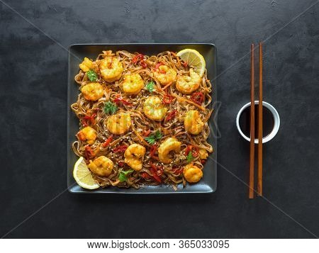 Stir Fry Noodles With Fried Shrimps, Vegetables And Soy Sauce. Asian Food Background.