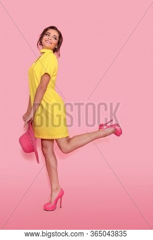 Young Smiling Woman In Yellow Dress And Hat Is Looking To Camera At The Pink Copy Space. Full Length
