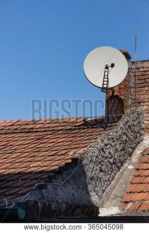Satellite Television Antenna On The Vintage Roof Tiles