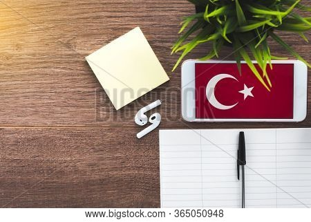 Learning Turkish, A Smartphone With A Turkish Flag And A Notebook For Writing Foreign Words On A Woo