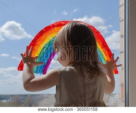A Happy Little Girl Looks Out The Window With A Painted Rainbow. Everything Will Be Alright. A Girl