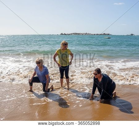 Group Of Three Senior Women Laughing As Falling Down In The Water On Beach. Humor Senior Health