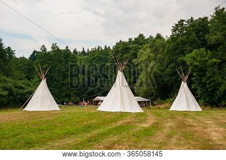 Beautiful View Of Three Tipi Tents In A Field. Tee Pee Built On Green Grass. Traditional Teepee Tent