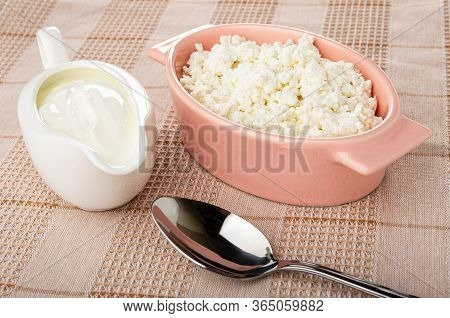 White Sauceboat With Sour Cream, Defatted Grained Cottage Cheese In Pink Glass Bowl, Spoon On Checke