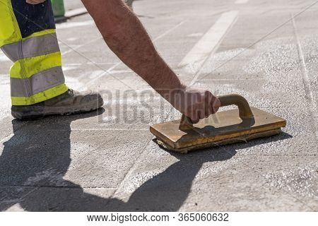 Road Workers With Tiler Tools At Work - Close-up Of Tiler