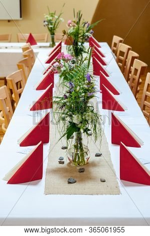 Red And White Indoor Catering Dinner At Summer Wedding With Homemade Meadow Flower Decoration. White