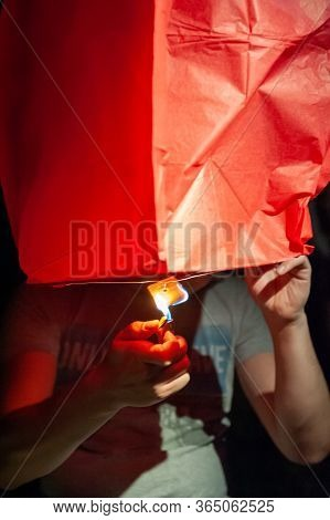 Couple Launching Sky Lantern. Ignite Flying Lantern, Floating Lantern, Hot-air Balloons On Dark Nigh