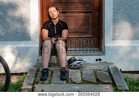 Cyclist Resting In Front Of Wooden Door On The Small Road. A Woman Cyclist Relaxing After Sport. Clo