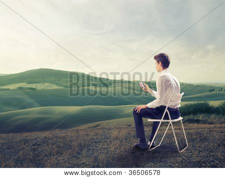 Young businessman sitting on a chair on a green meadow and using a mobile phone