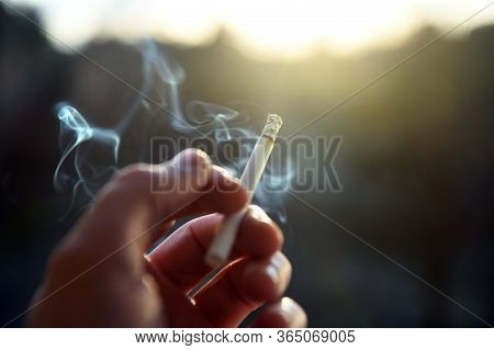 The Hand Of A Man Holding A Smoking Cigarette In His Fingers, Which The Owner Smokes While Somewhere