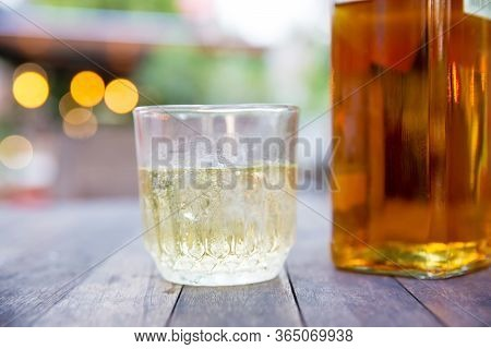 Close Up Booze Glass, Booze Bottle On The Wood Table With Bokeh Light And Blur Background. Hang Out