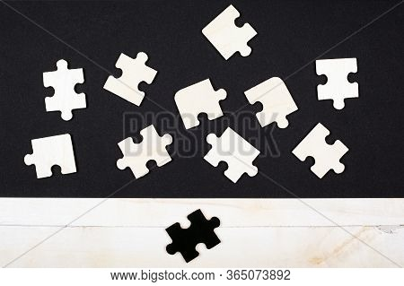 White Wooden Puzzles On A Black Background And One Black Puzzle On A White Background Close-up Top V