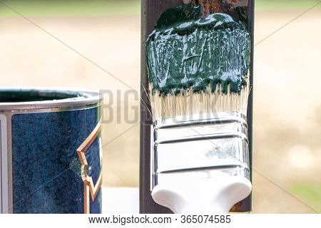 Can Of Green Paint. Brush Painting Metal Profile. Painting A Metal. Open Jar Of Green Paint. Tin Of