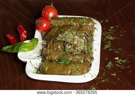Caucasian Dolma Is A Dish Of Grape Leaves And Rice With Meat. Serving Dolma With Yogurt Sauce And Sp