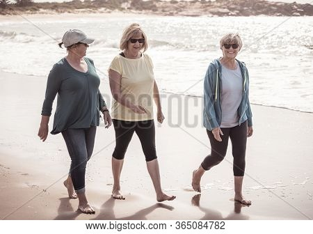 Lovely Group Of Three Active Senior Woman On Their 60s Walking, Exercising And Having Fun On The Bea