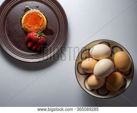 Aerial Image Of A Homemade Flan With A Decorative Strawberry, And Several Free-range Eggs In A Bowl