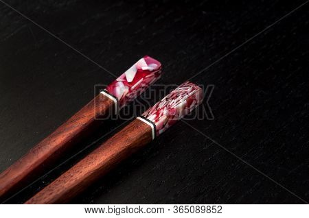 Wooden Chopsticks With Colorful Stone Detail On The Top. Dark Background