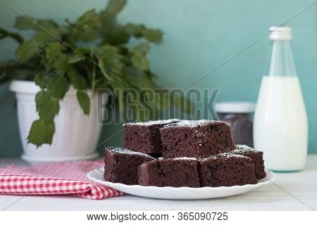 Pieces Of Chocolate Cake On A White Plate And A Red And White Checkered Napkin. Dessert, Milk And Ch