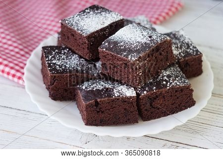 Chocolate Cake Cut Into Square Pieces, Sprinkled With Icing Sugar On A Plate, White Background