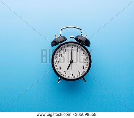 Black Vintage Alarm Clock On Blue Background Isolated Ticking Seven O Clock. Morning Wake Up And Tim