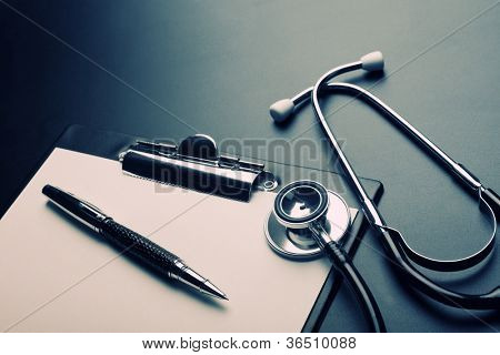 Clipboard, pen and medical stethoscope. Toned