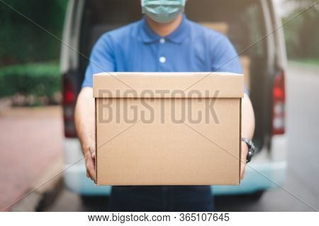 Postal Delivery Courier Man Wearing Protective Face Mask In Back Of Cargo Van Delivering Package Hol