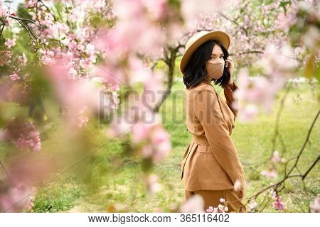 Woman Posing Wearing Face Mask Decorated With Flowers. Stylish Handmade Cotton Mask. Spring Blossom