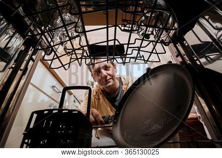 A Young Man Puts A Frying Pan In The Dishwasher. Inside View Of A Dishwasher. Washing Dirty Dishes A