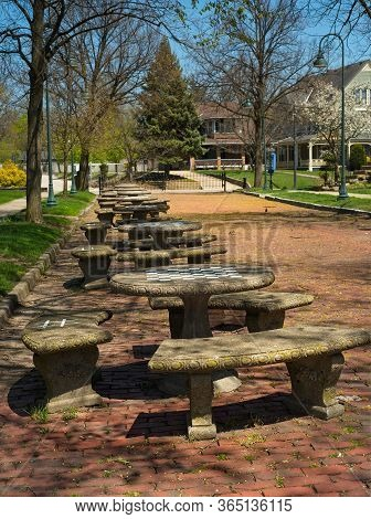 A Row Of Stone Tables Occupies An Old Brick Street Next To An Ohio Village Commons; Each Table Has A