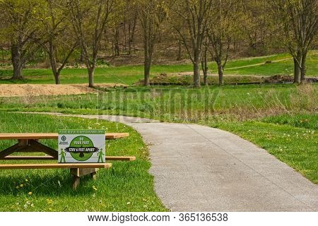 Walton Hills, Oh, Usa - May 3, 2020: A Cleveland Metroparks Sign On A Picnic Table Bench In The Bedf