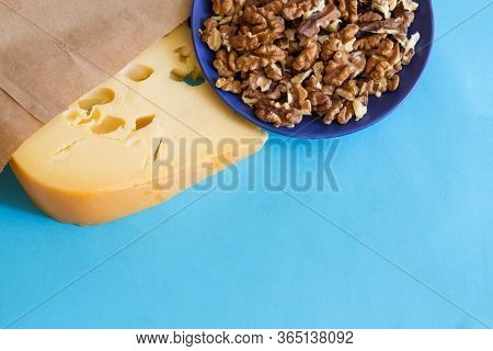 Cheese With Wallnuts. Delicious Snacks On Blue.