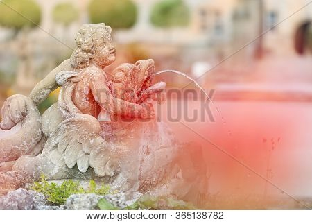 White Statue Of Angel Boy Fountain In Weikersheim, Bavaria, Germany. Europe Travel.