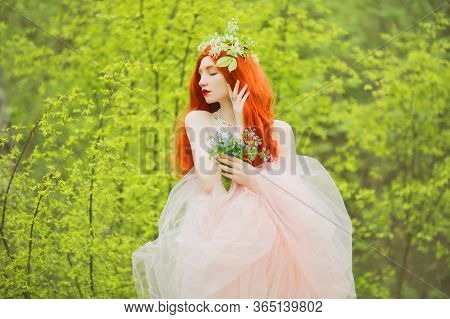 Young Unusual Pale Girl With Curly Hair On A Spring Background. Ring With A Blue Stone On The Finger